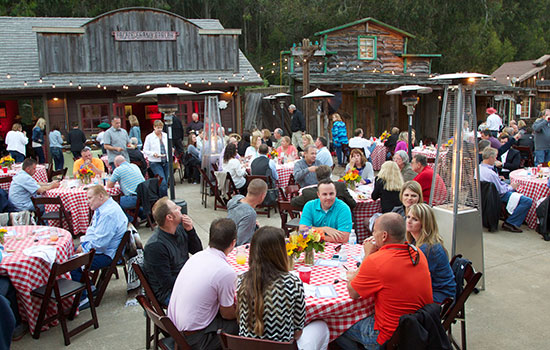 People sit at tables outdoors at an event