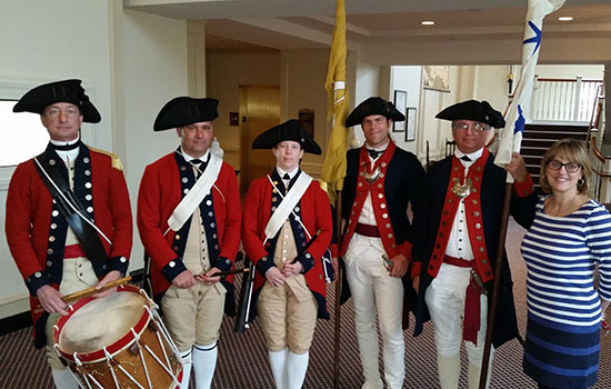Patti stands with soldiers in Revolutionary War uniforms